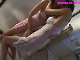 2 κορίτσια σε υγρός clothes φιλιά patting υπό ο μπάνιο