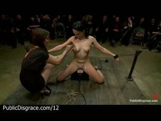 Clamped babe on sybian in public