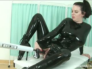 Dark haired chick in latex gets fucked by huge black cock on fucking machine