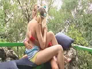 Blonde lesbian friens outside on a chair