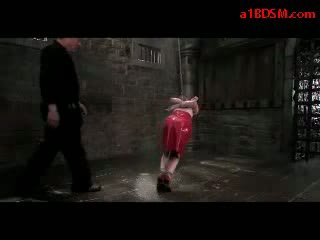 Redhead Girl In Latex Skirt Hanging In Bondage Tortured With Stick And Water By Master In The Dungeon