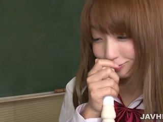 Japanese schoolgirl put a flute up to ...